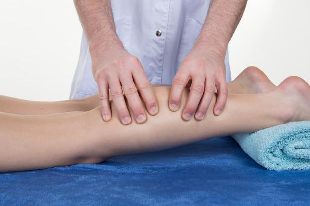 Massagem na panturrilha de uma jovem garota muito magra
