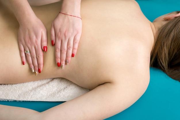 Massagem nas costas com óleo para uma jovem