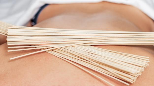 Massagem nas costas com vassouras de bambu