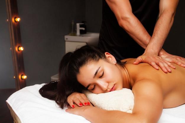 Massagem nas costas. massagem terapêutica clássica. garota em um procedimento de massagem nas costas.