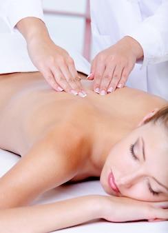 Massagem nas costas para a jovem bonita