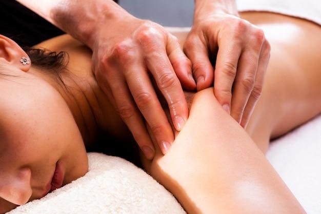 Massagem nas costas para uma mulher. massagem curativa, médica e relaxante. fundo de férias.