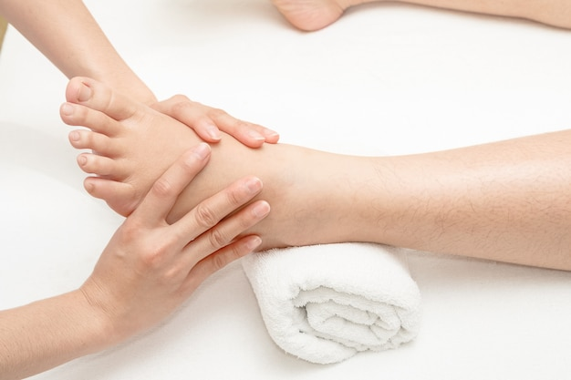 Massagem nos pés, as mãos do terapeuta massageando o pé feminino