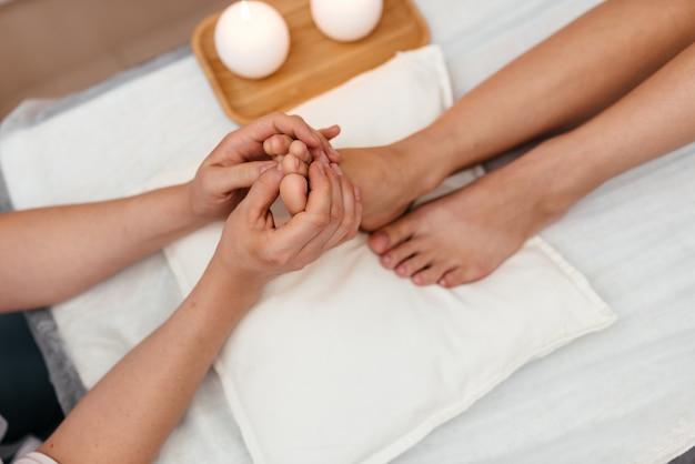 Massagem nos pés. massagista massageando o pé da mulher.