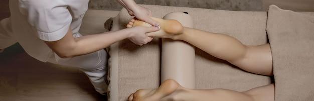 Massagem nos pés na sala de massagens - as mãos femininas fazem massagens nos pés femininos - beleza e saúde.