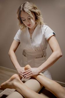 Massagem nos pés nas mãos femininas da sala de massagens massageia a beleza e a saúde dos pés femininos.
