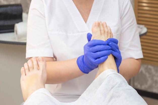 Massagem nos pés no salão spa, closeup. massagem nos pés relaxar cuidados com a pele. pedicure terapêutico.