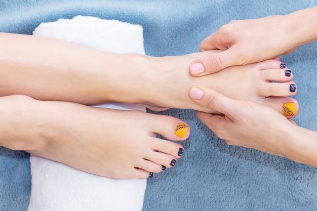 Massagem nos pés no salão spa, closeup. massagem nos pés relaxar cuidados com a pele.