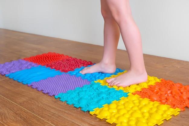 Massagem nos pés. os pés das crianças andam em tapetes ortopédicos. tratamento e prevenção de pés chatos e doenças nas pernas