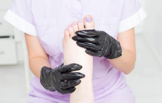 Massagem nos pés. relaxar. o pedicure mestre faz uma massagem nos pés. massoterapeuta.
