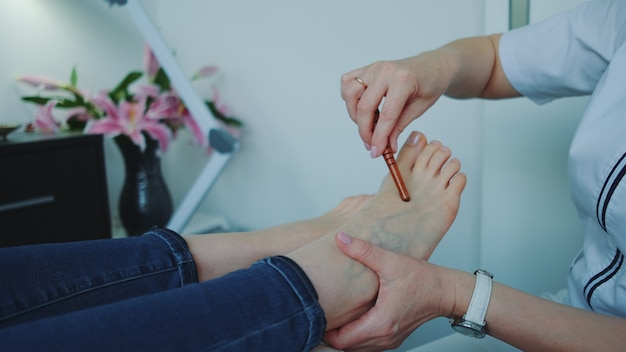 Massagem nos pés shiatsu usando uma varinha no salão de beleza.