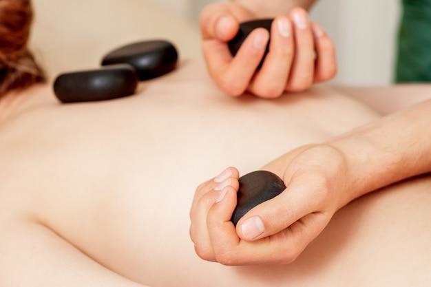 Massagem pedras nas costas feminina.
