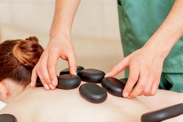 Massagem pedras nas costas.