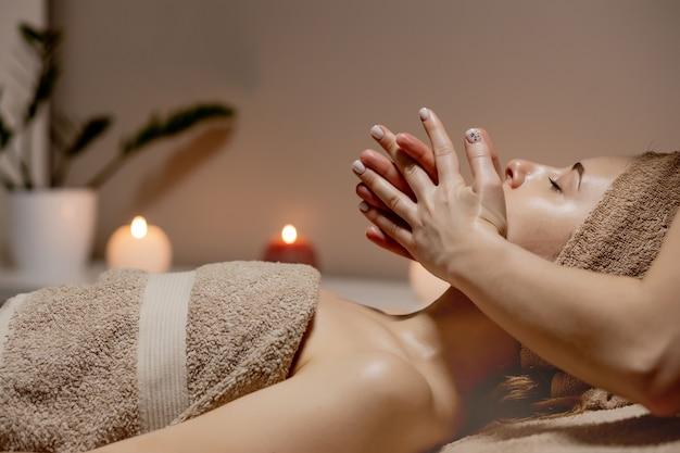 Massagem relaxante mulher recebendo massagem na cabeça em salão de spa