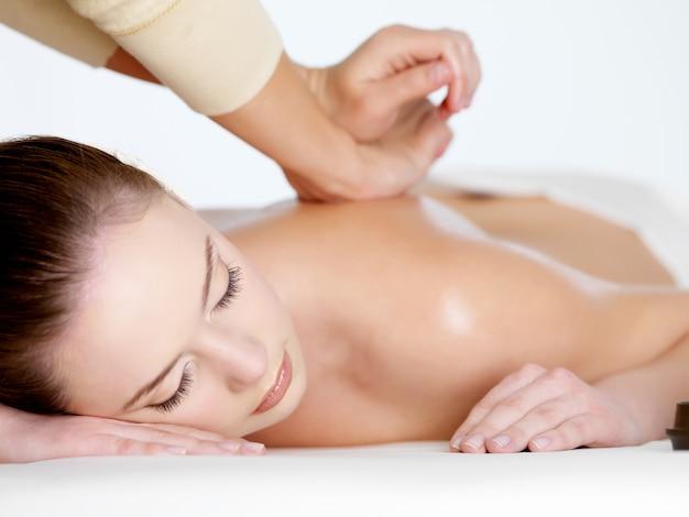 Massagem relaxante nas costas para jovem mulher bonita