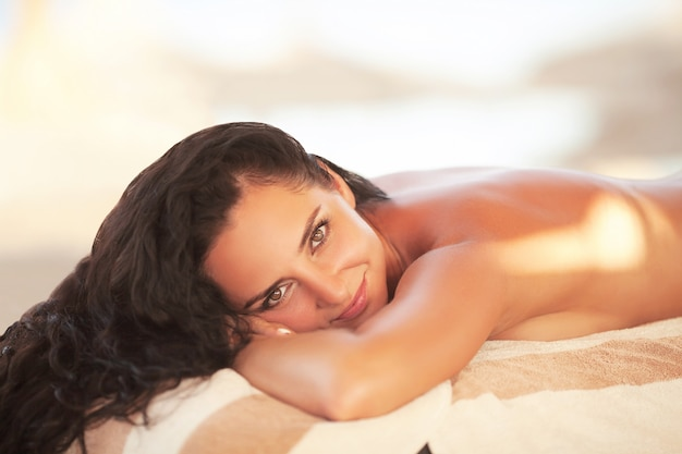 Massagem spa. mulher sorridente relaxada, recebendo uma massagem nas costas