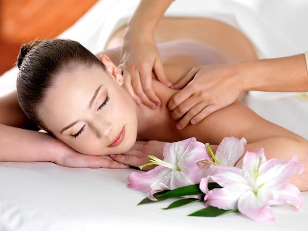 Massagem spa no ombro para jovem mulher bonita em salão de beleza