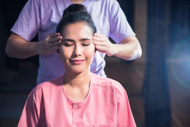 Massagem tailandesa de reflexologia da cabeça para uma jovem e bela mulher asiática no spa