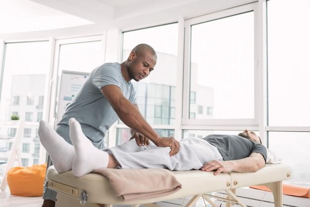 Massagem terapêutica. homem bonito sério e simpático olhando para as pernas de seus pacientes enquanto se prepara para uma massagem