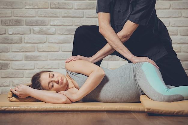 Massagem tradicional tailandesa de mulher grávida deitada no tapete em estúdio de ioga. jovem massagista branca vestida com uniforme preto estica o corpo com as mãos. parede de tijolos ao fundo. conceito de saúde