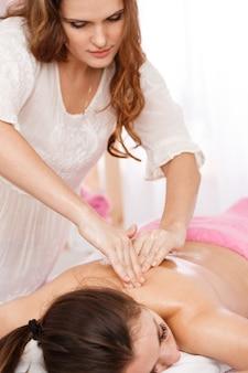 Massagista atraente dando massagem na coluna trabalhando no salão brilhante
