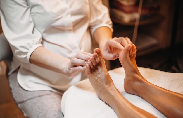 Massagista caucasiana está fazendo uma massagem nos pés para o cliente durante um procedimento de spa
