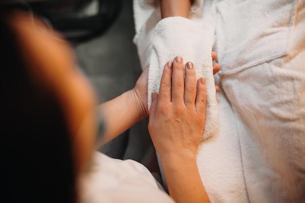 Massagista caucasiana está secando a mão do cliente com uma luva especial após terminar a sessão de massagem