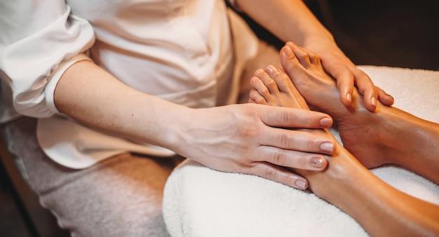 Massagista caucasiana fazendo uma sessão de massagem nas pernas com a cliente deitada no sofá