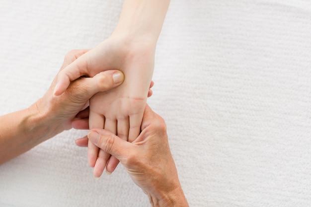 Massagista cortada dando massagem nas mãos de mulher