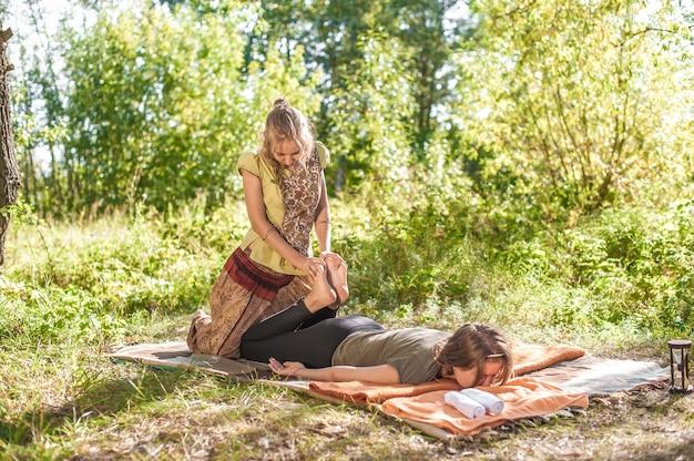 Massagista de menina implementa suas habilidades de massagem no solo da floresta.