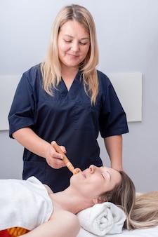 Massagista de mulher massageia o rosto da garota usando um massageador de rolo de madeira, estrutura vertical. cuidados com o rosto e pescoço. massagem facial de drenagem linfática com massageador de madeira