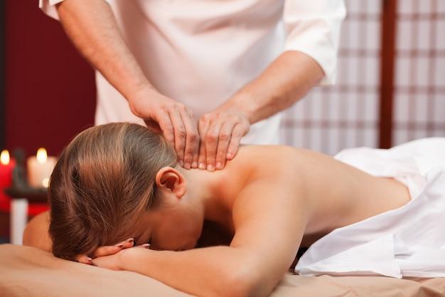 Massagista de spa profissional massageando o pescoço de uma cliente do sexo feminino. mulher relaxante durante a massagem relaxante de corpo inteiro. foto recortada de um terapeuta de spa trabalhando. serviços de resort. tradições, viajando
