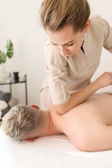 Massagista de tiro médio com cliente