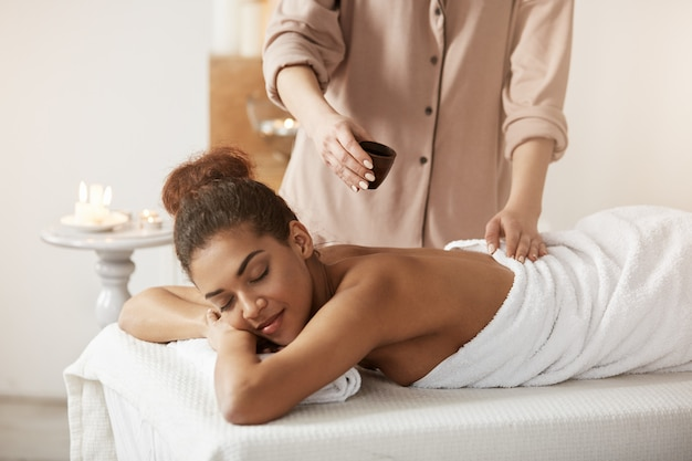 Massagista, derramando óleo fazendo massagem para linda mulher africana no salão spa.