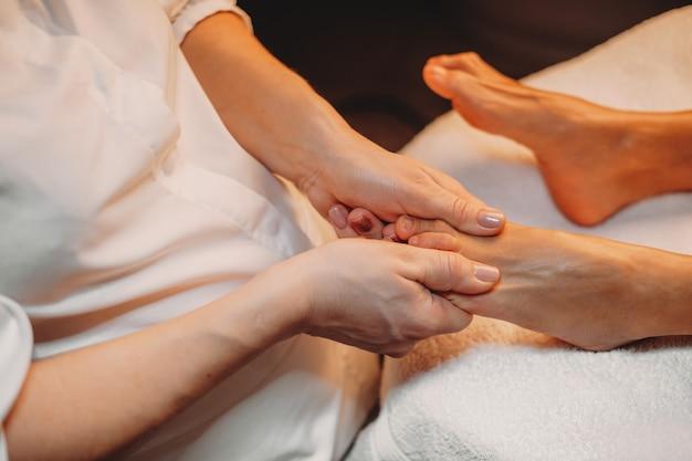 Massagista está trabalhando com as pernas do cliente durante um procedimento de spa no salão