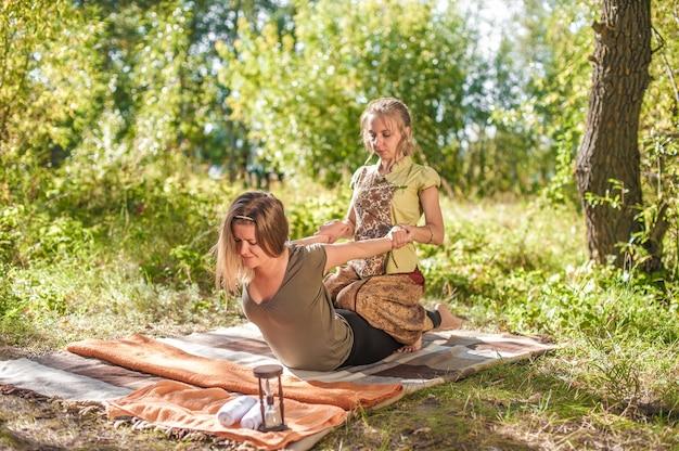 Massagista experiente aplica suas habilidades de massagem em seu cliente no chão.