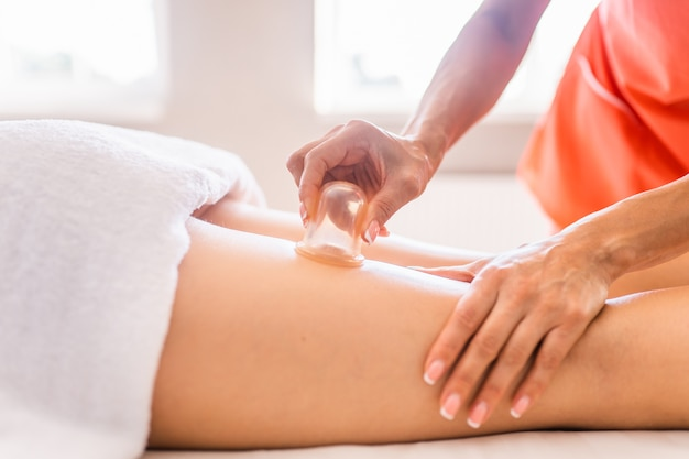 Massagista faz massagem com potes de celulite nas nádegas e coxas da paciente