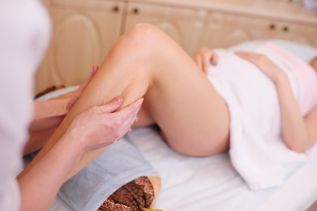Massagista faz uma massagem nos pés para uma mulher grávida