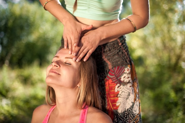 Massagista faz uma massagem refrescante em seu cliente no solo da floresta.