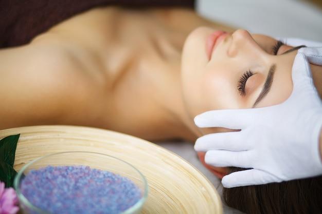 Massagista fazendo massagem a cabeça de uma mulher em salão de spa