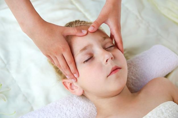 Massagista fazendo massagem de rosto para criança.