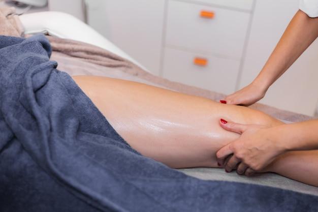 Massagista fazendo massagem manual para cliente no salão de beleza do spa usando óleo