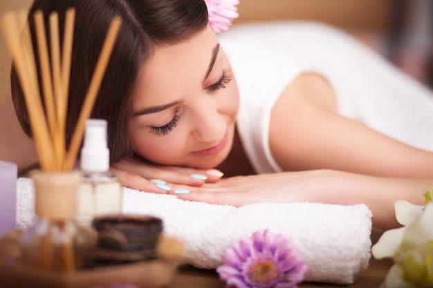 Massagista fazendo massagem na parte de trás da mulher no salão spa.