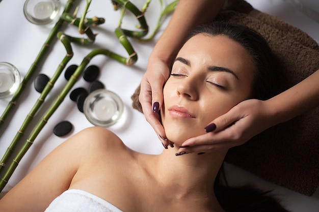 Massagista fazendo massagem no corpo da mulher no salão spa.