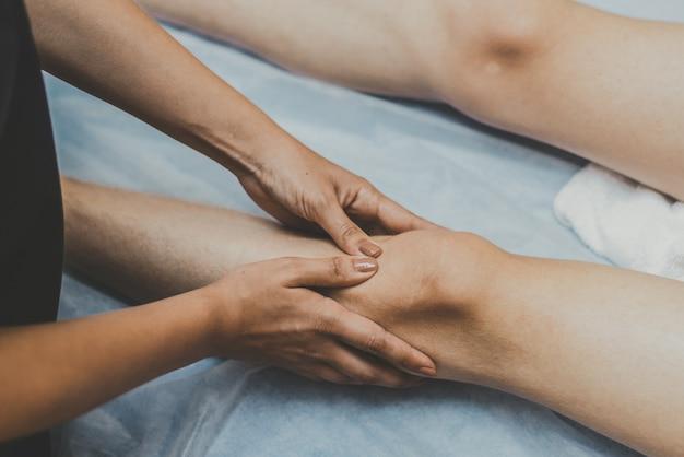 Massagista fazendo massagem no joelho para o jovem. o médico massageia a perna para tratamento