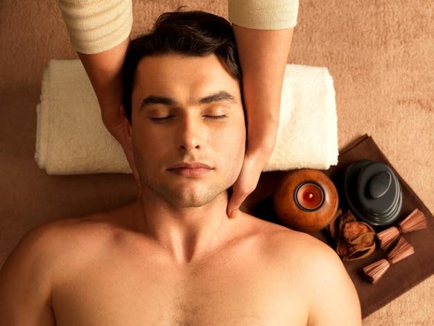 Massagista fazendo massagem no pescoço do homem no salão spa.