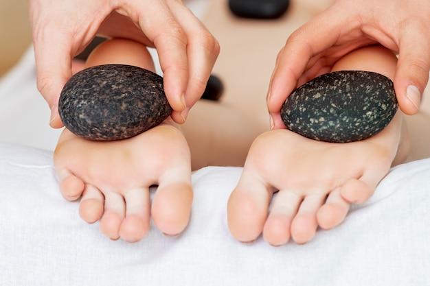 Massagista fazendo massagem nos pés com pedras.