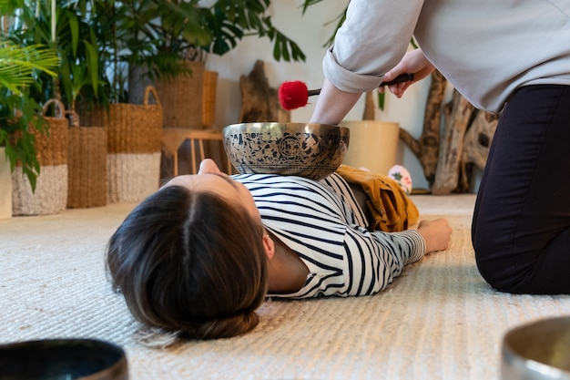 Massagista fazendo massagem tradicional tibetana de terapia sonora cantando em uma mulher relaxada