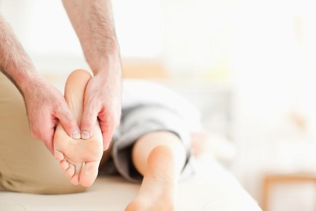 Massagista masculino massageando os pés de uma mulher