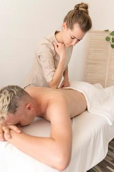 Massagista massageando homem